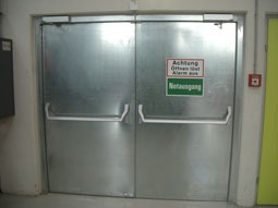 Bild mit Tür mit Paniktürverschlüssen und Notausgangsbeschilderung
