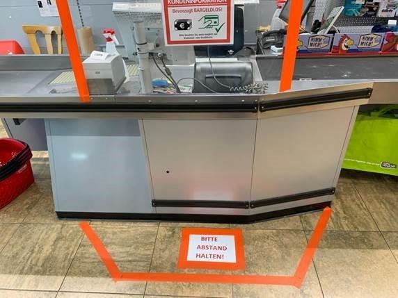 Bild zeigt Abstandshinweis vor einer Supermarktkasse in Form einer Bodenmarkierung