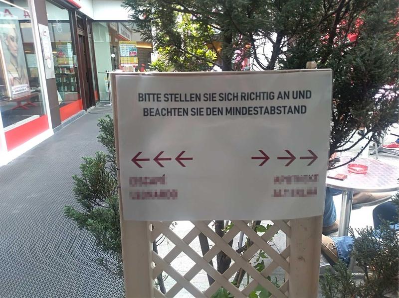 Zwei nebeneinanderliegende Geschäfte definieren mit Hinweisschildern Zugänge, um den Kundenstrom zu regeln und einen geordneten Zugang zu ermöglichen.